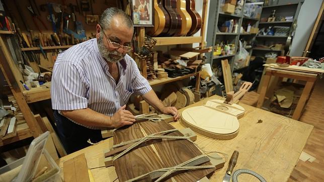 Rafael Romero sujeta una de las tapas de madera de una de las partes de la guitarra, en su taller