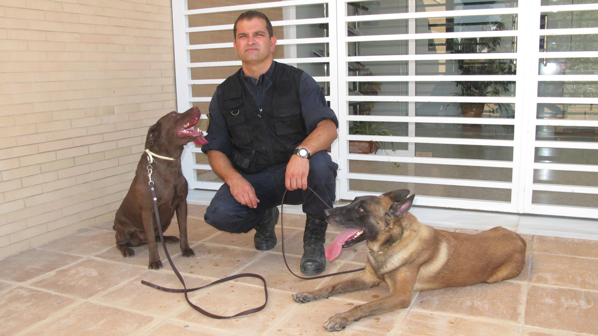 Miguel Ángel Romero con dos de los perros de la Unidad Canina de El Cuervo