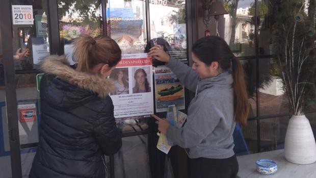 Dos colaboradores de la familia pegando carteles en Tavira (Portugal)