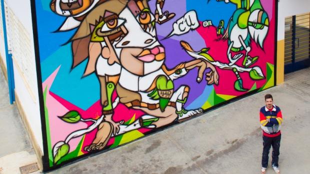 Denis Due junto al mural que ha realizado para el colegio La Alunada