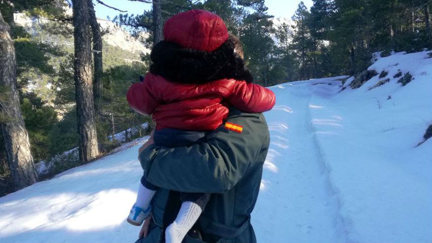 Un agente de la Guardia Civil lleva en brazos a uno de los niños rescatados