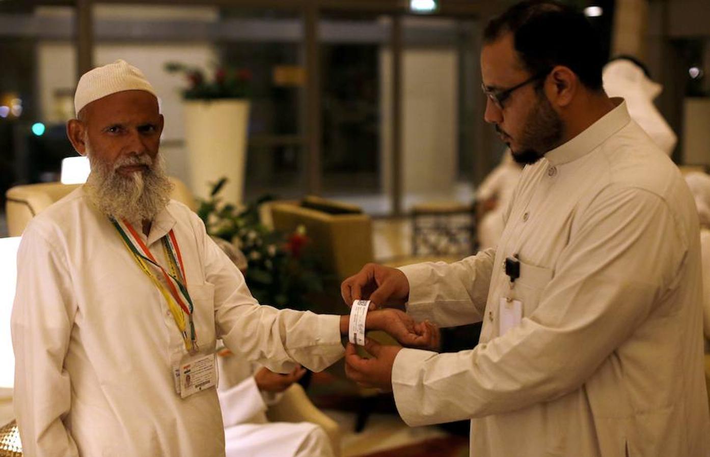 Un funcionario saudí ajusta un brazalete de identificación electrónica que las autoridades están dando a los peregrinos durante la peregrinación anual «Hajj» musulmana en la ciudad santa de La Meca