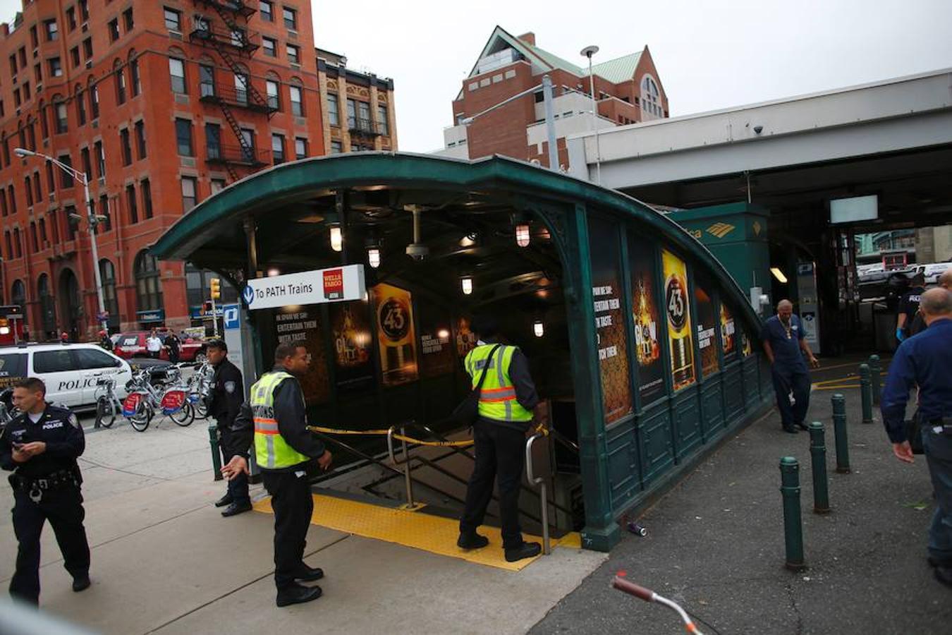 Los trabajadores del servicio de emergencia se reúnen fuera de la estación ferroviaria de Hoboken, Nueva Jersey