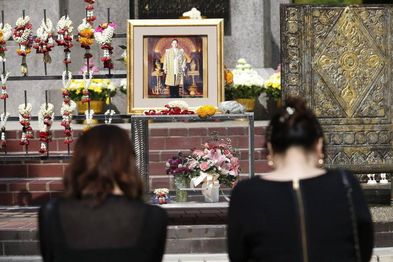 Tailandeses muestran su respeto mientras esperan el inicio del cortejo fúnebre del Rey Bhumibol Adulyadej