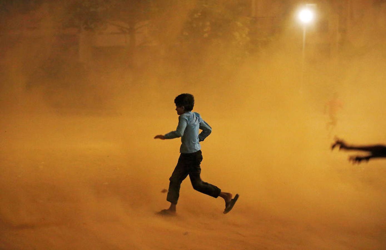 Un niño corre durante la tormenta de arena en Nueva Delhi