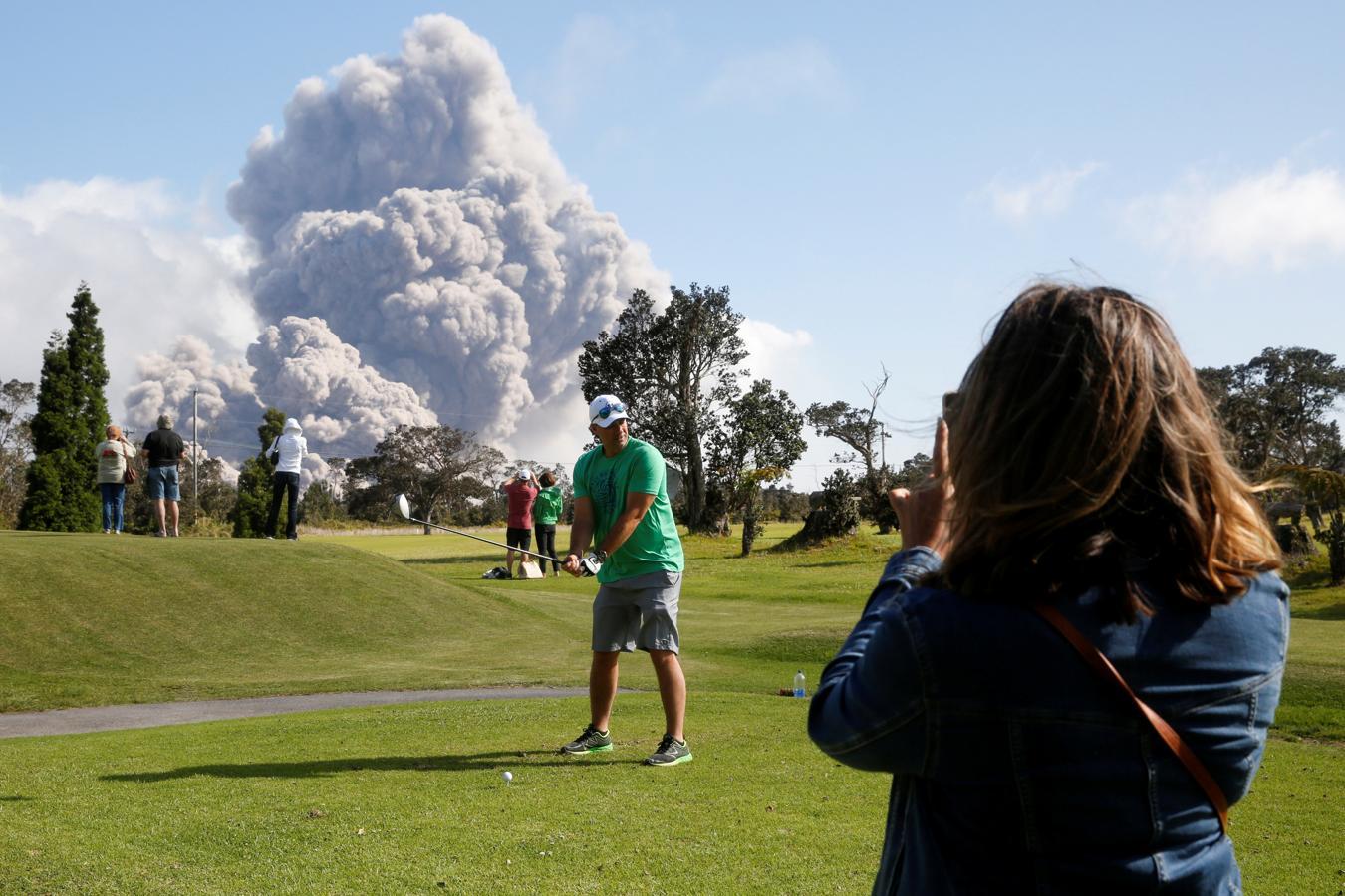 Un hombre juega al golf con la erupción de cenizas de fondo