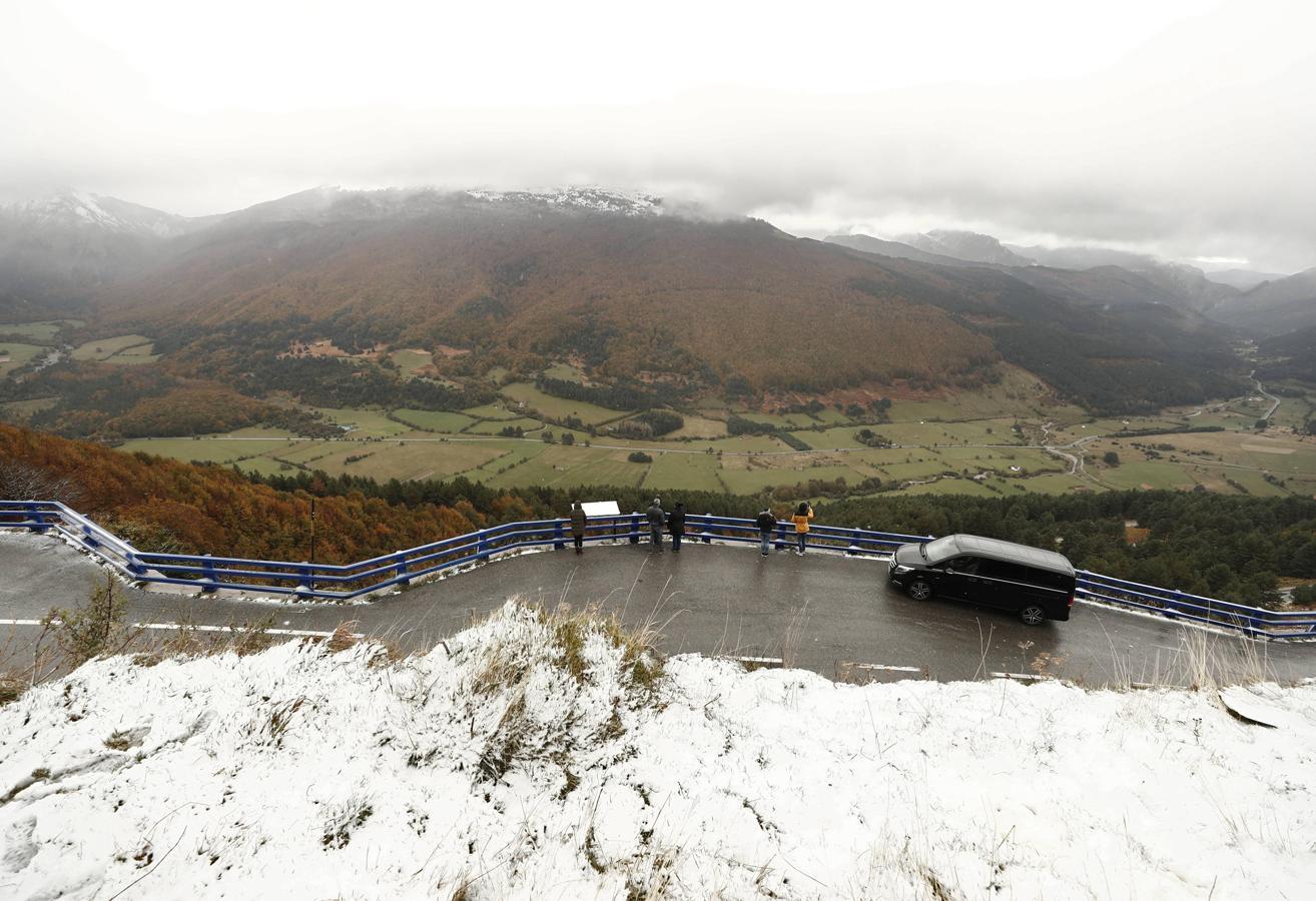 Un grupo de personas observan desde un mirador el valle de Belagoa (Navarra) cuyos bosques presentan los colores típicos del otoño y donde la nieve caída ha dejado una estampa invernal.
