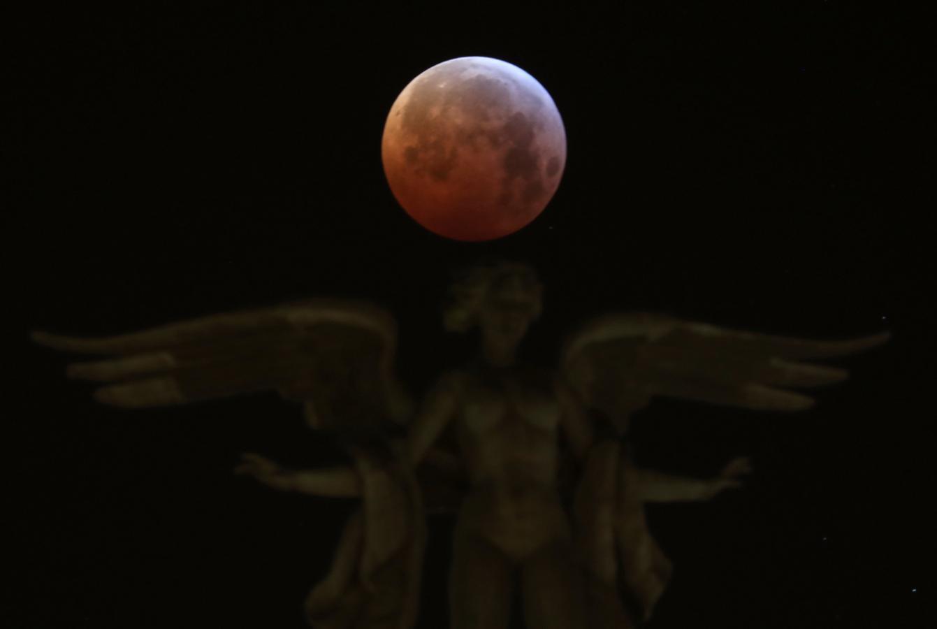 La superluna de sangre de lobo, vista sobre el edificio de «Metrópolis», en la esquina de las calles Alcalá y Gran Vía en Madrid