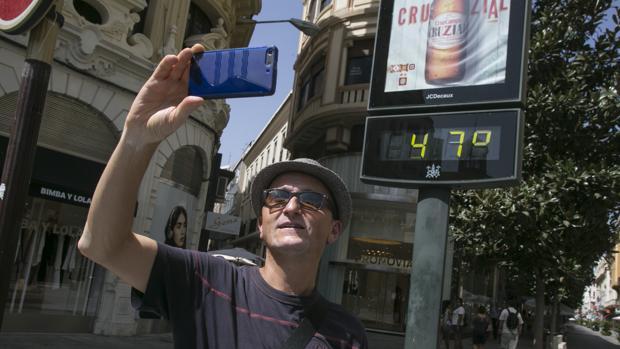 Un hombre se hace un «selfie» con un termómetro en el centro