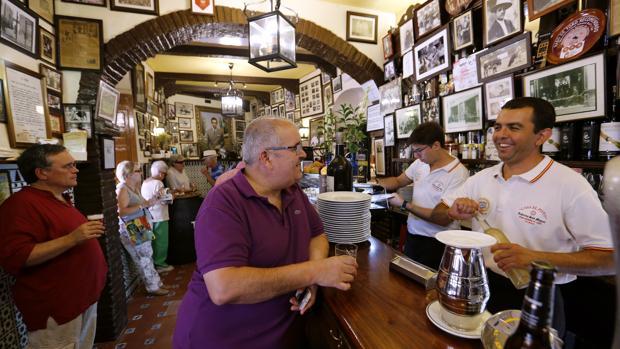 Varias personas toman un vino en una taberna