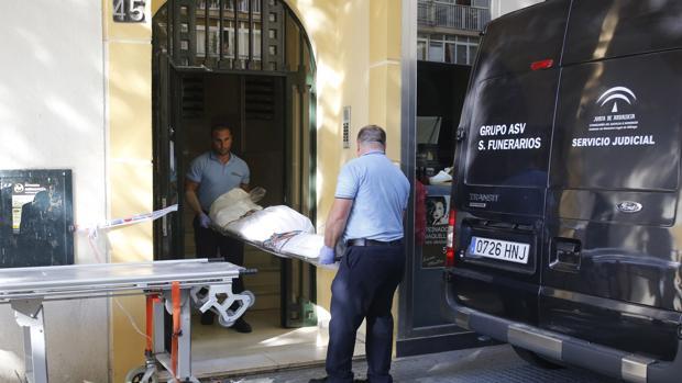 Uno de los cadáveres, en el momento de ser trasladado desde la casa familiar para su examen forense