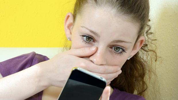 Una joven observa los mensajes en su móvil