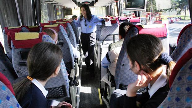 Alumnos atienden a las explicaciones de la conductora de un autobús escolar