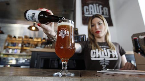 Una camarera sirve una cerveza Califa