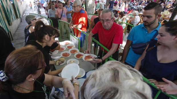 Varios vecinos hacen cola para probar un plato de la «salmorejá»