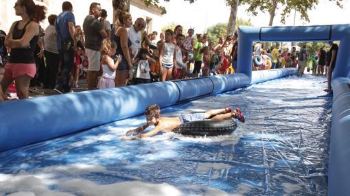 Un niño se desliza por el tobogán acuático de la Velá