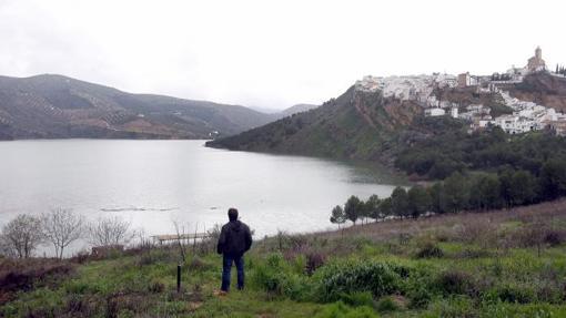 Un vecino contempla las aguas del pantano con Iznájar al fondo
