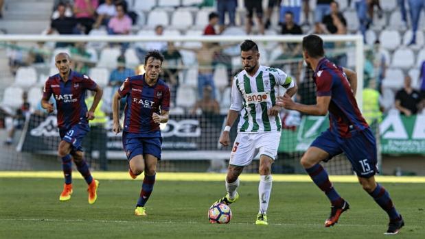 El capitán del Córdoba CF, Luso, conduce el balón ante varios rivales del Levante