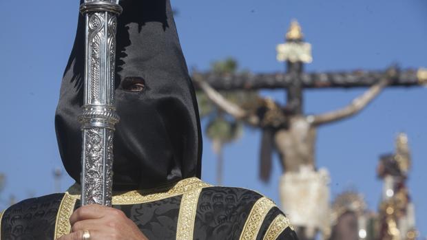 Nazareno del Cristo de Gracia con el paso del Crucificado al fondo