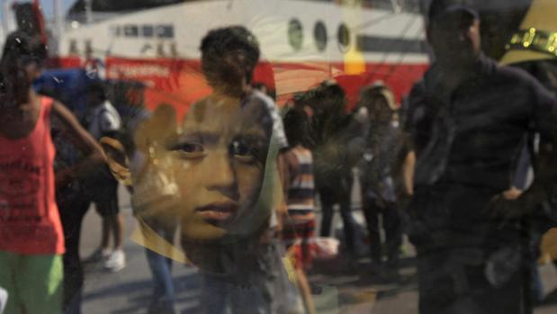 Un niño mira a través de un autobús camino de un campo de refugiados en Grecia
