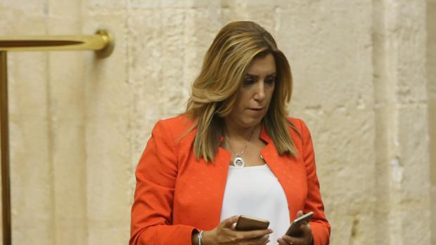 Susana Díaz, con dos teléfonos, en el último Pleno del Parlamento la pasada semana