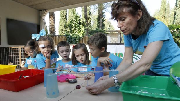 Varios niños atienden las explicaciones de una docente en el Jardín Botánico