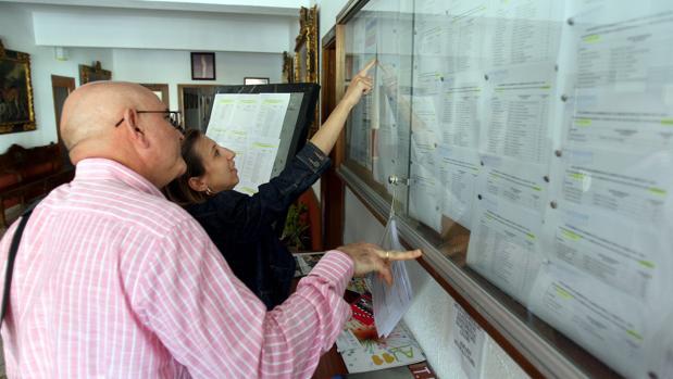 Dos personas consultan las listas de escolarizacion en un centro