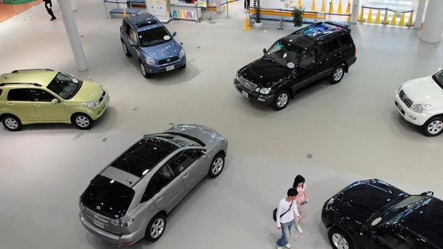 Una pareja pasea entre coches en exposición