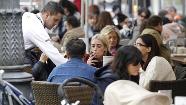 Un camarero atiende a unos clientes en una terraza