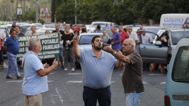 Rafael Salazar, en el centro, organiza a los vecinos del Higuerón en el corte de ayer en La Victoria