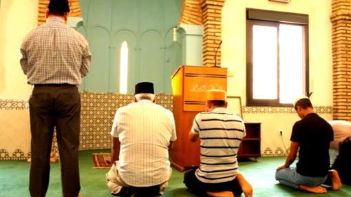 Un grupo de fieles ahmadíes, postrados en dirección a La Meca, orando en el interior de la mezquita