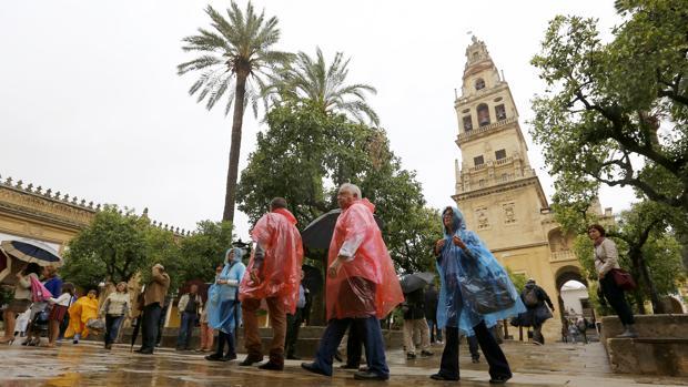 Turistas bajo la lluvia, ayer en el Patio de los Naranjos
