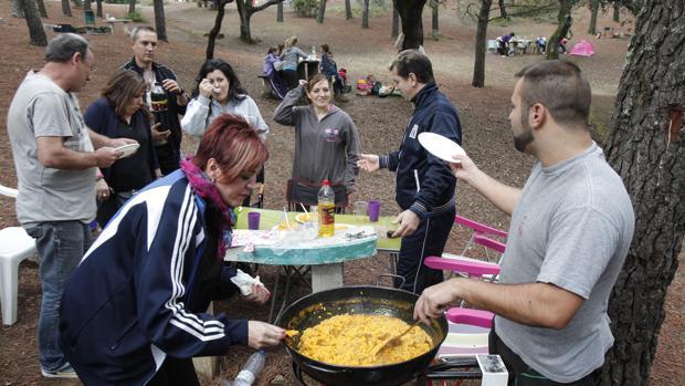 Una familia degusta un perol de arroz en el parque de Los Villares