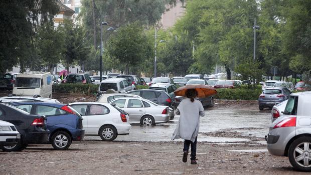 Una mujer atraviesa el solar, inundado por las lluvias, entre los coches aparcados