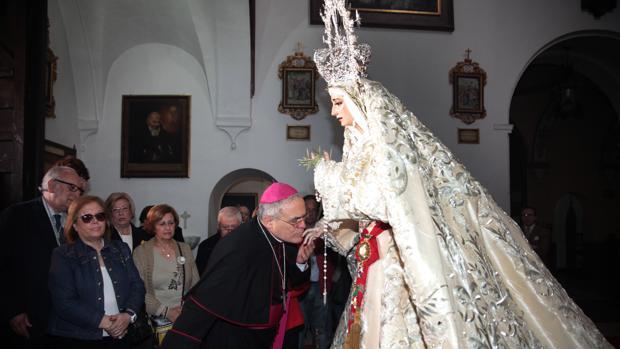 El obispo de Córdoba besa la mano de la Virgen de la Paz