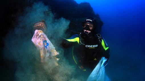 Un voluntario limpia el fondo de plásticos