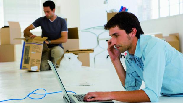 Un empresario utiliza su portátil mientras habla por teléfono