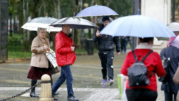 Varias personas con paraguas ante el parque de Colón