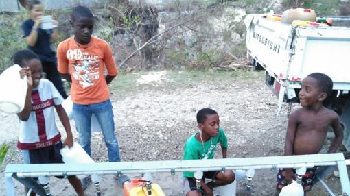 Niños bebiendo en una de las instalaciones montadas por Bomberos sin Fronteras
