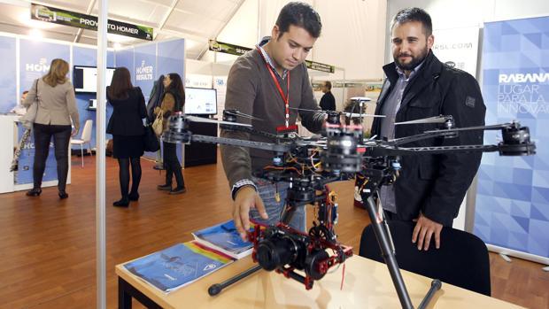 Dos participantes en Fimart 2014 contemplan un dron en uno de los expositores