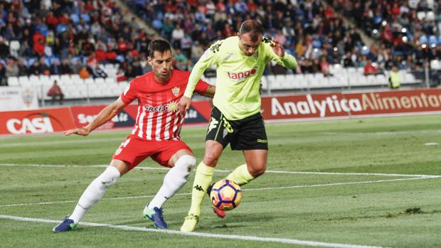 Un momento del partido entre el Córdoba CF y el Almería, Juli presionado por Trujillo