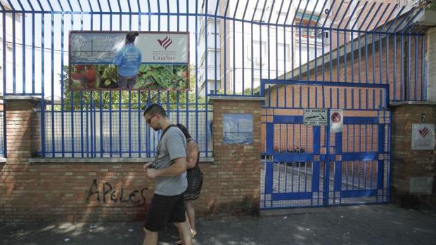 Dos personas pasean delante de la Fundación Guadalquivir