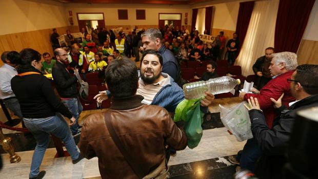 El líder de los parcelistas, Rafael Salazar, con una botella de agua sucia