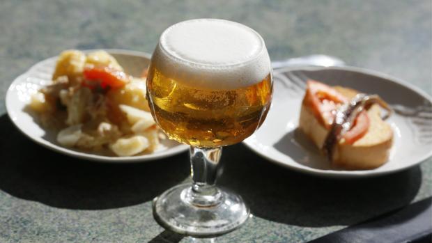 Una caña de cerveza con dos tapas