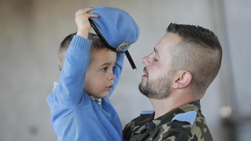 Un niño juega con la boina azul de su padre, que ya está de camino a Líbano