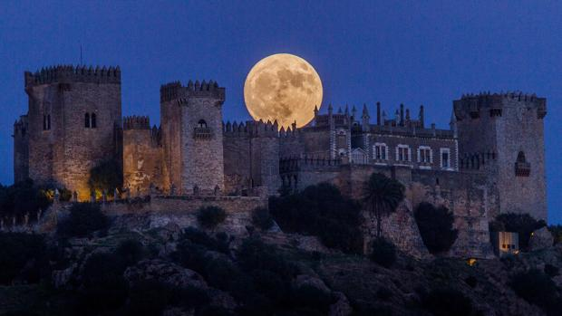 La luna se esconde tras la fortaleza de la Vega cordobesa
