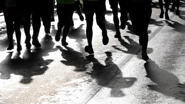 Las piernas de un grupo de atletas populares en un día mojado