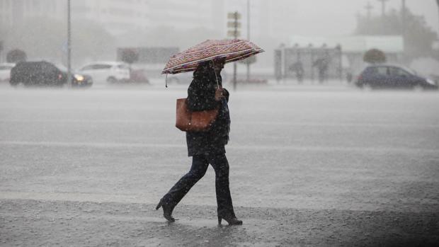Una señora camina bajo una intensa lluvia en el centro de Córdoba
