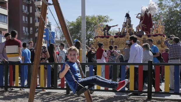 Un niño juega al paso de la hermandad de la Merced