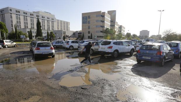 Un hombre cruza los terrenos encharcados donde se ubica el parking actual